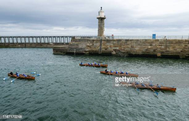 Rowing crews head into the harbour as they approach the finish of their race during the annual Whitby Regatta on August 10 2019 in Whitby England At...