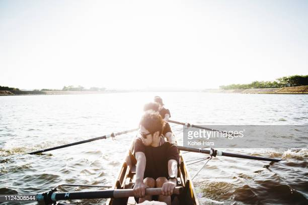 rowing team in scull on the river - team sport stock pictures, royalty-free photos & images