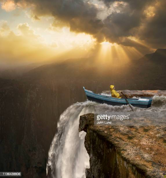 rowing towards catastrophic, dangerous waterfall - pericolo foto e immagini stock