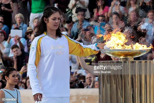 Rowing World Champion Katerina Nikolaidou of Greece lights the cauldron during the handover ceremony for the Olympic torch at Panathinean stadium on...