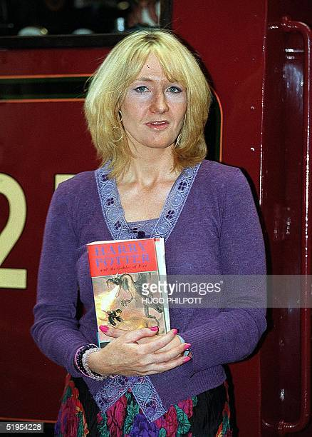 K Rowling the authoress of the successful Harry Potter books poses for the cameras with the new Harry Potter adventure at King's Cross station in...
