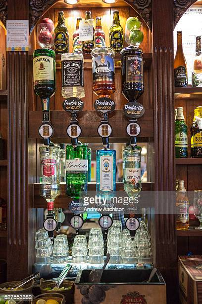 Rows of alcohol spirit bottles hanging in an English pub in London A pub is a drinking establishment and is a fundamental part to British culture and...