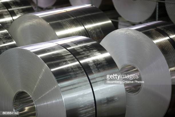 Rows of aluminum coils sit on the floor of a manufacturing facility