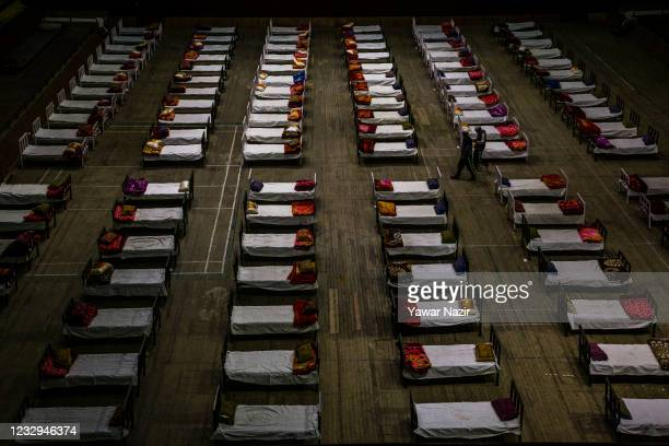 Rows of beds are placed inside indoor sports stadium as a makeshift Covid-19 isolation center, on May 17, 2021 in Srinagar, the summer capital of...