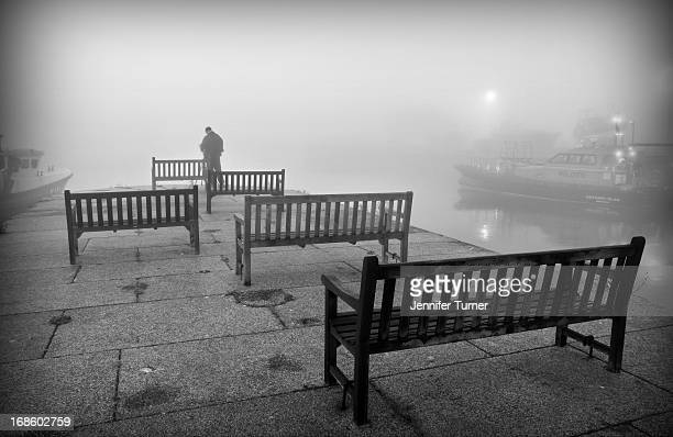 Rows of benches at Ramsgate harbour on a foggy sunrise in autumn. Black and white shot of photographer setting up a shot