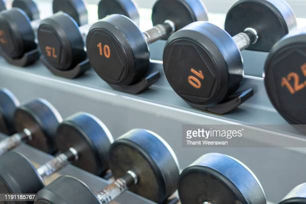 rows of black metal dumbbells in the gym, selective focus. - mass unit of measurement stock pictures, royalty-free photos & images