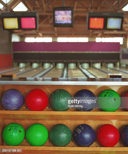 Rows of bowling balls on rack in bowling alley