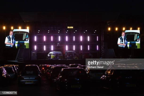 Rows of cars are parked in front of the stage to watch British Bassbaritone Paul Sheehan at the start of Puccini's La bohème performed by members of...