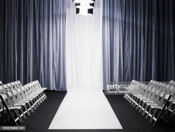 rows of chairs beside catwalk - sfilata di moda foto e immagini stock