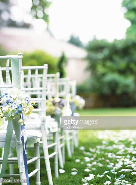 Rows of chairs beside grassy aisle (focus on chair in foreground)