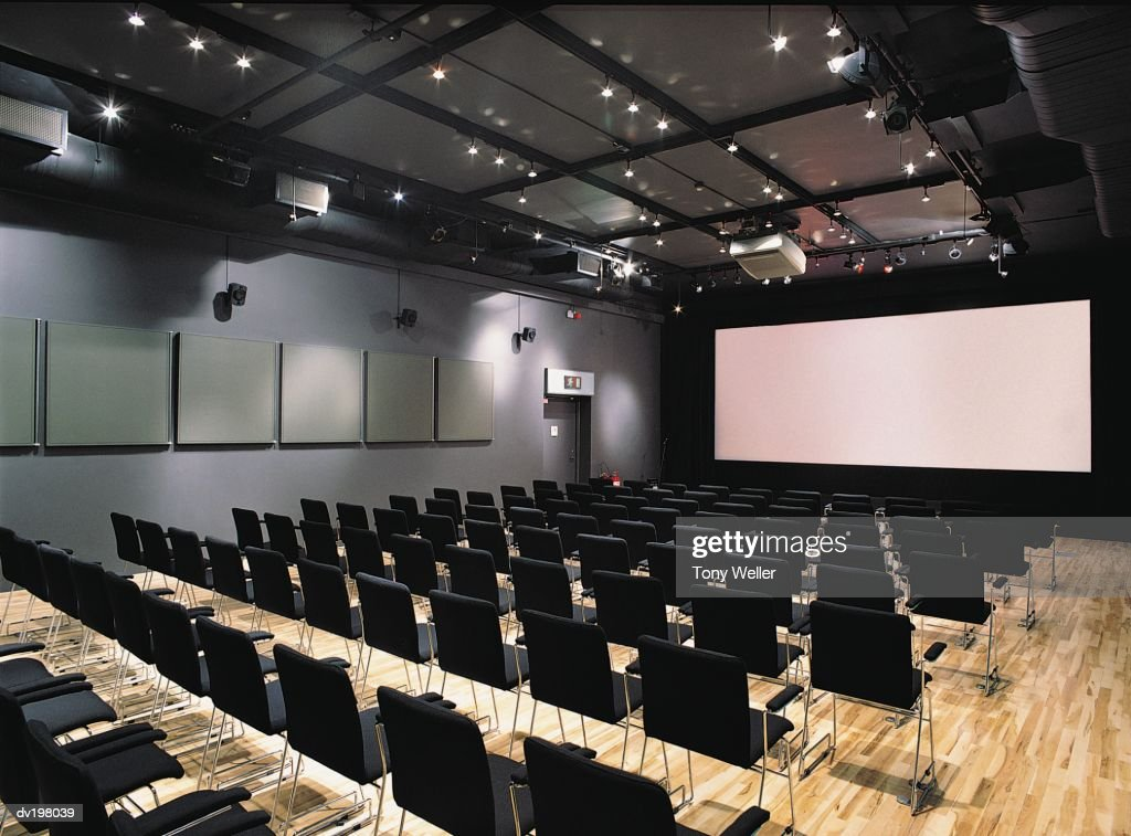Rows of chairs facing a projection screen : Stock Photo