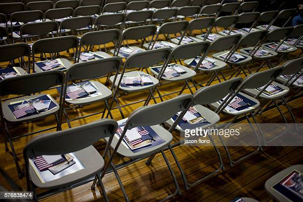 Rows of chairs with American flags laid on them in preparation for a naturalization ceremony
