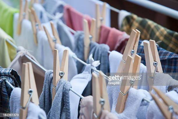 Rows of clothing hanging on a line with pegs