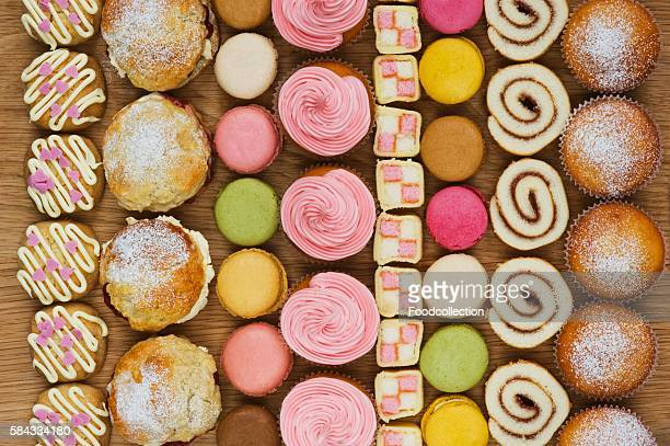 rows of cupcakes, scones, macarons, swiss rolls and pieces of mini-battenburg cake - battenburg stock pictures, royalty-free photos & images