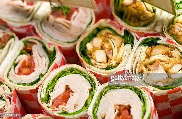 Rows of deli wrap sandwiches with various fillings