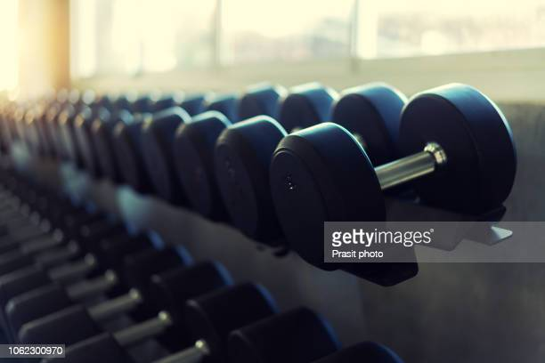 rows of dumbbells in the gym. color tone and glare of the sun - mass unit of measurement stock pictures, royalty-free photos & images