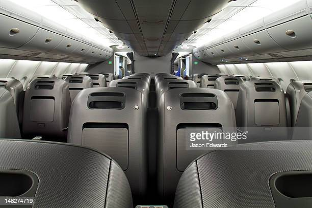 Rows of empty graphite business class passenger seats in a plane cabin.