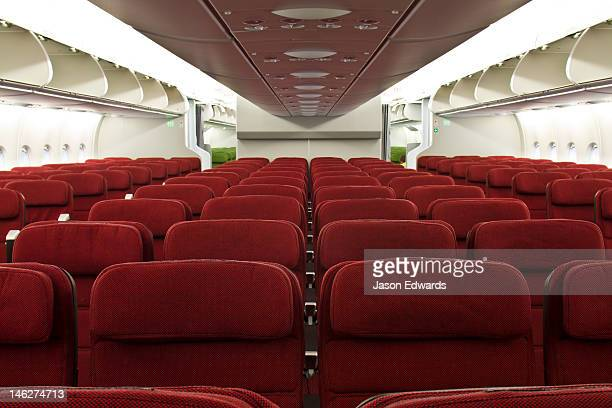 Rows of empty red economy class passenger seats in a plane cabin.