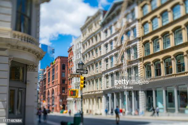 rows of loft apartment buildings stand along both side of street in soho district at new york city ny usa on may 16 2019. - ニューヨーク ソーホー ストックフォトと画像