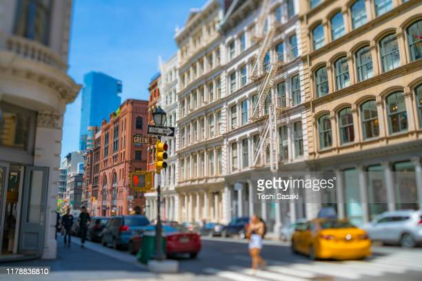 rows of loft apartment buildings stand along both side of street in soho district at new york city ny usa on may 18 2019. - ニューヨーク ソーホー ストックフォトと画像
