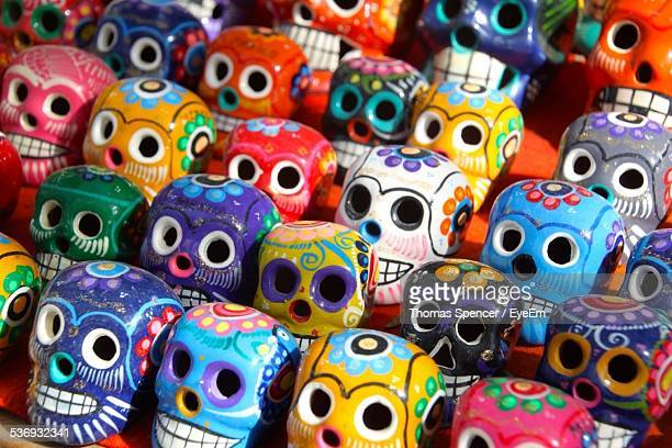 rows of multi colored ceramic skulls for sale - dia de muertos fotografías e imágenes de stock