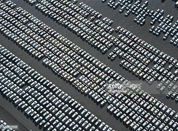 Rows of new cars parked in parking lot, aerial view
