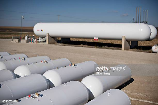 Rows of new liquid propane storage tanks foreground sit near a large storage tank at Michlig Energy in Manlius Illinois US on Thursday Nov 20 2014...