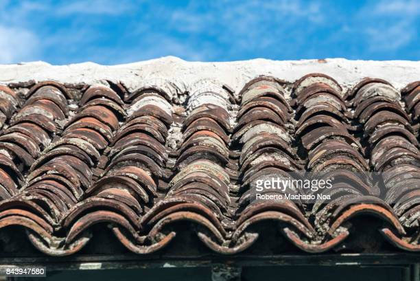 Rows of old clay pantiles laid on a roof timeworn and blackened they are