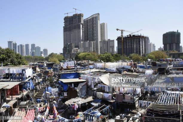 Rows of openair laundry stalls known as Dhobi Ghat are pictured against a backdrop of highrise buildings in India's most populous city Mumbai on...