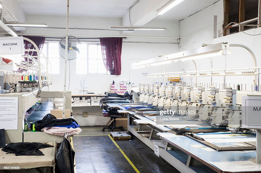 Rows of programmed embroidery machines speed stitching cloth in clothing factory : Stock Photo