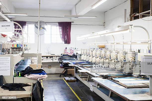 rows of programmed embroidery machines speed stitching cloth in clothing factory - stiches stock photos and pictures