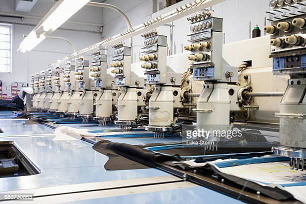 rows of programmed embroidery machines speed stitching in clothing factory - stiches stock photos and pictures