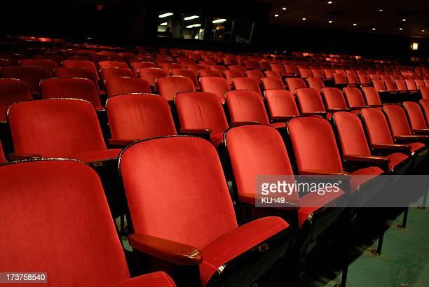 列の赤色の空のシアター席。