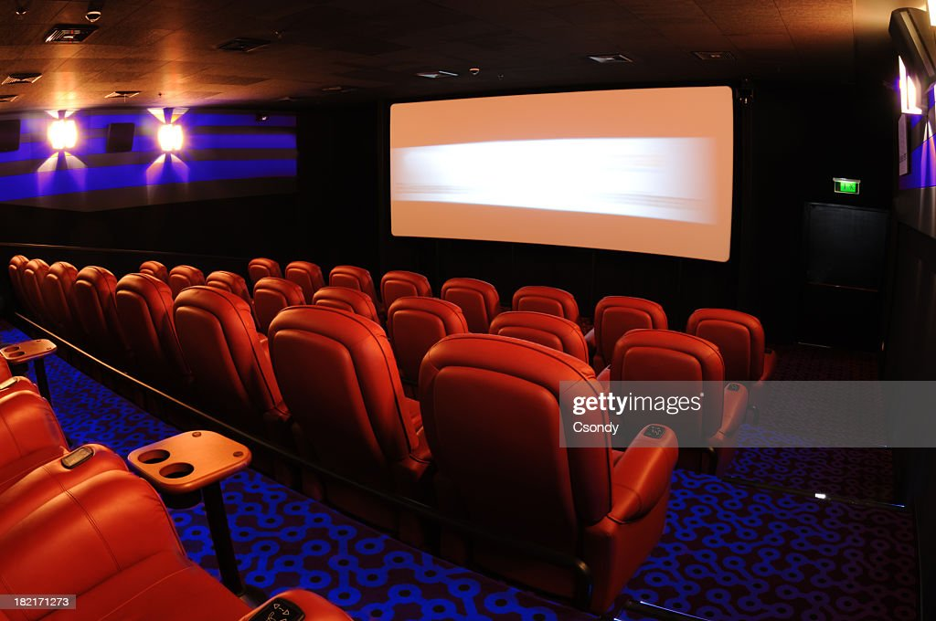 Rows of red movie theater seats facing the movie screen : Stock Photo