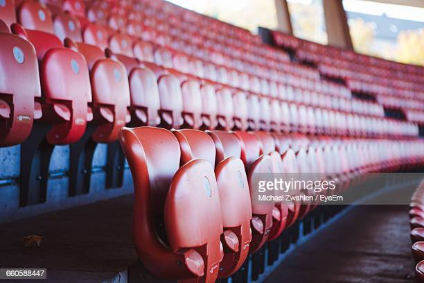 rows of red seats in sports stadium - empty bleachers stockfoto's en -beelden