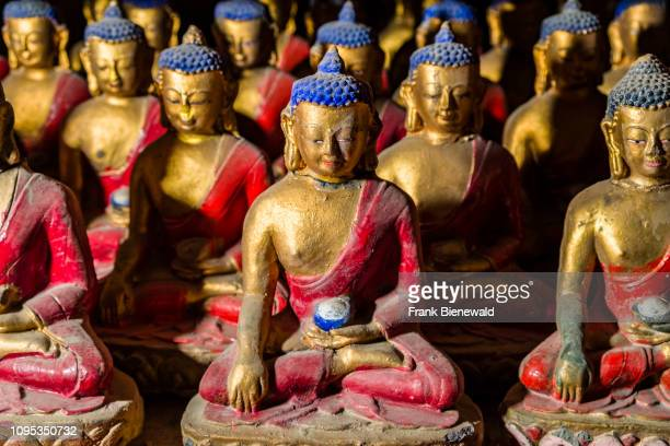 Rows of small red and golden painted Buddha statues inside Braga Gompa the local monastery