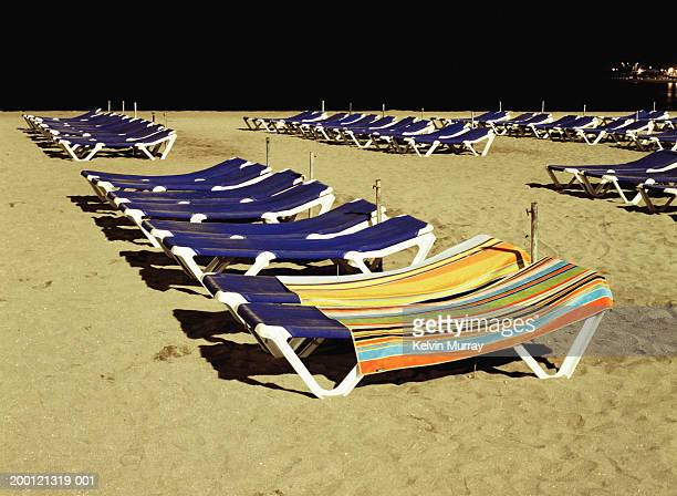 Rows of sun loungers on beach, two covered with towels, night