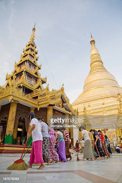 Rows of sweepers follow one another to clean the ground around the Shwedagon pagoda at regular intervals throughout the day. This looks like...