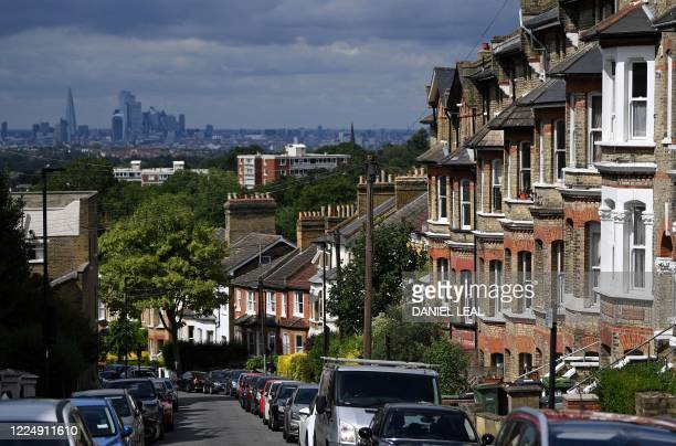 Rows of terraced houses and residential properties are pictured in south London on July 6 backdropped by the skyline of the City of London British...