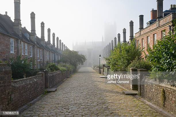 rows of terraced houses at vicars close on a misty morning with wells cathedral in the far distance in the town of wells in somerset. - somerset england stock pictures, royalty-free photos & images