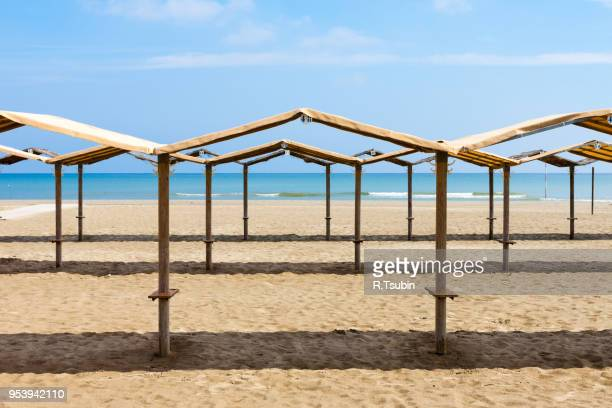 rows of the palm leaf sun shades on the beach in italy - liguria stock photos and pictures
