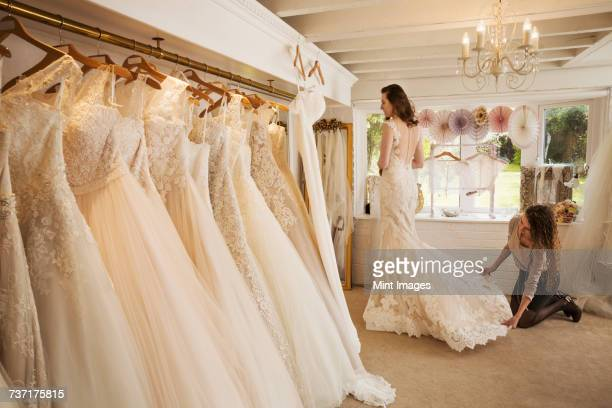 rows of wedding dresses on display in a specialist wedding dress shop. - ウェディングドレス ストックフォトと画像