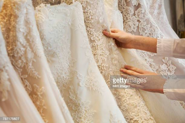 rows of wedding dresses on display in a specialist wedding dress shop. close up of full skirts, some with a lace overlay, in a variety of colour tones. . - robe de mariée photos et images de collection