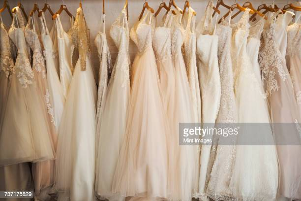 rows of wedding dresses on display in a specialist wedding dress shop. a variety of colour tones and styles, fashionable lace and boned bodices.  - robe de mariée photos et images de collection