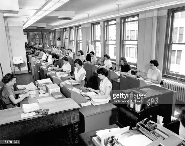 Rows of women office workers entering data using keypads and punch cards at the Erie Railroad offices Cleveland Ohio circa 1960