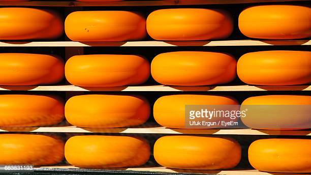 rows of yellow gouda cheese on shelf - netherlands stock pictures, royalty-free photos & images