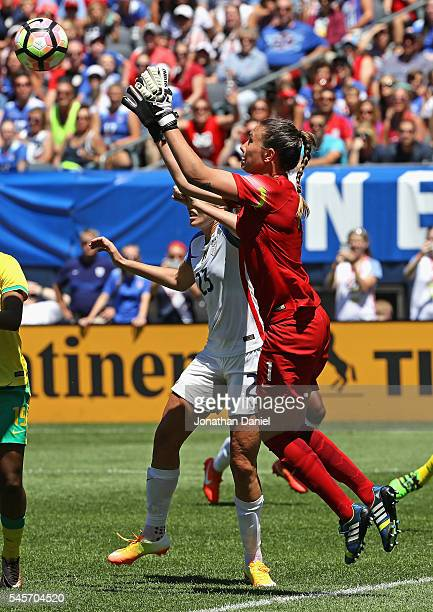 Roxanne Barker of South Africa leaps to make a save over Allie Long of the United States during a friendly match at Soldier Field on July 9 2016 in...