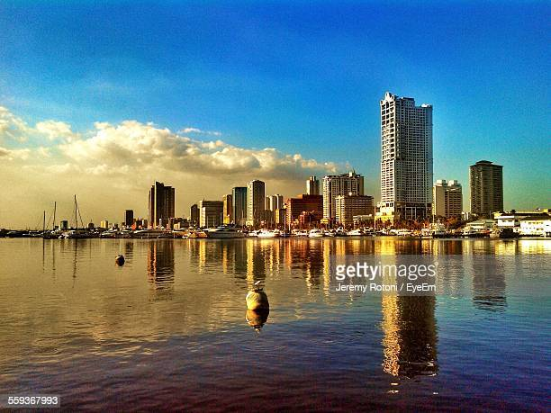 roxas boulevard reflected on water against blue sky - manila philippines stock pictures, royalty-free photos & images