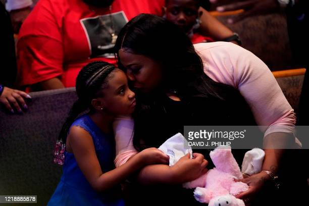 Roxie Washington holds Gianna Floyd the daughter of George Floyd as they attend the funeral service for George Floyd at The Fountain of Praise church...