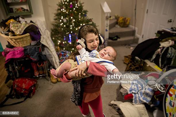 Roxy Rovin holds her younger brother Finn who is sporting a festive menorah bib in the family's living room The family is also helping their mom Amy...